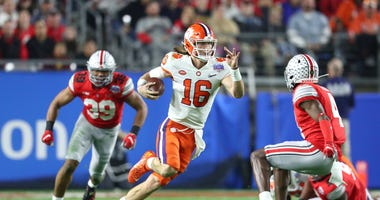 Clemson Tigers quarterback Trevor Lawrence (16) runs the ball against the Ohio State Buckeyes during the fourth quarter in the 2019 Fiesta Bowl college football playoff semifinal game at State Farm Stadium.
