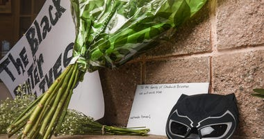 A memorial with a poster, card for the Boseman family and flowers are left at the front door of T.L. Hanna High School in Anderson, S.C. Monday, August 31, 2020.