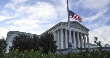 The United States Supreme Court with American flag at half staff as people mourn outside of the United States Supreme Court on Saturday, September 19, 2020 after Court Justice Ruth Bader Ginsburg died on Friday, September 18, 2020.