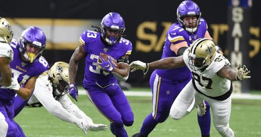 Jan 5, 2020; New Orleans, Louisiana, USA; Minnesota Vikings running back Dalvin Cook (33) runs the ball against New Orleans Saints defensive end Mario Edwards (97) during the first quarter of a NFC Wild Card playoff football game at the Mercedes-Benz Supe