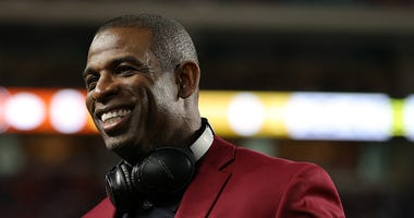 Deion Sanders smiles while being honored at the Super Bowl.