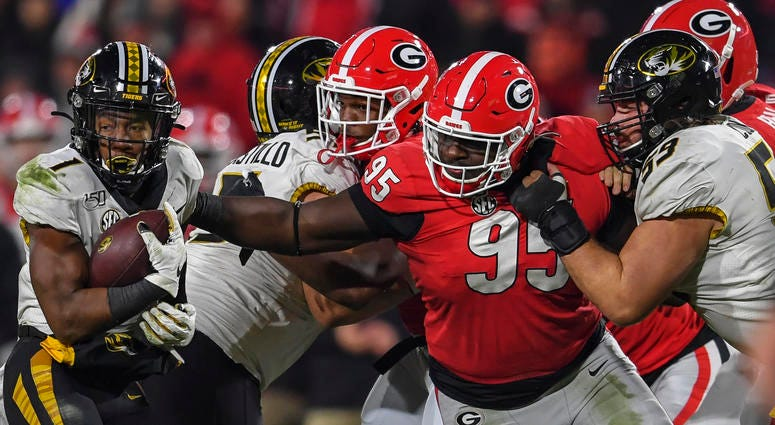 Nov 9, 2019; Athens, GA, USA; Missouri Tigers running back Tyler Badie (1) is tackled by Georgia Bulldogs defensive lineman Devonte Wyatt (95) during the second half at Sanford Stadium. Mandatory Credit: Dale Zanine-USA TODAY Sports